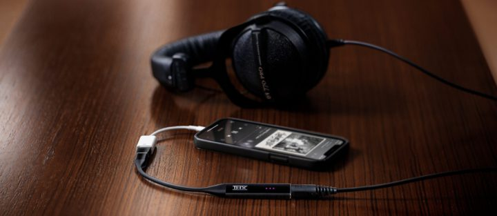 Image of a THX Onyx DAC connected to headphones and a smartphone